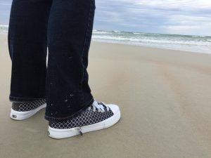 A photograph of my White Quarterfoil Pattern Black Background Zipz shoes at the Beach